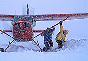 Conrad Anker and Tom Burt help freee a bush plane stucdk in fresh snow on the Ruth Glacier, Denali National Park, Alaska Range, Alaska