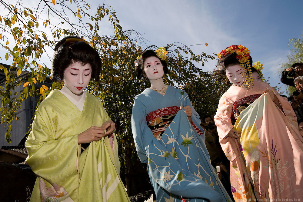 KYOTO-MAIKO .Memorial service for the poet Yoshii Isamu (1886-1960) who loved the Gion pleasure quarters. Geiko and maiko place flowers at a stone monument on which one of his poems is inscribed. Gion Shinbashi, just north of Shijo. Kyoto, 8 November 2007.