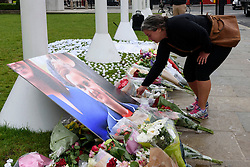 © Licensed to London News Pictures. 17/06/2016. A Well wisher lays flowers and tributes in Parliament Square in memory of Labour party MP JO COX.  She was allegedly attacked and killed by suspect 52 year old Tommy Mair close to Birstall Library near Leeds.  London, UK. Photo credit: Ray Tang/LNP