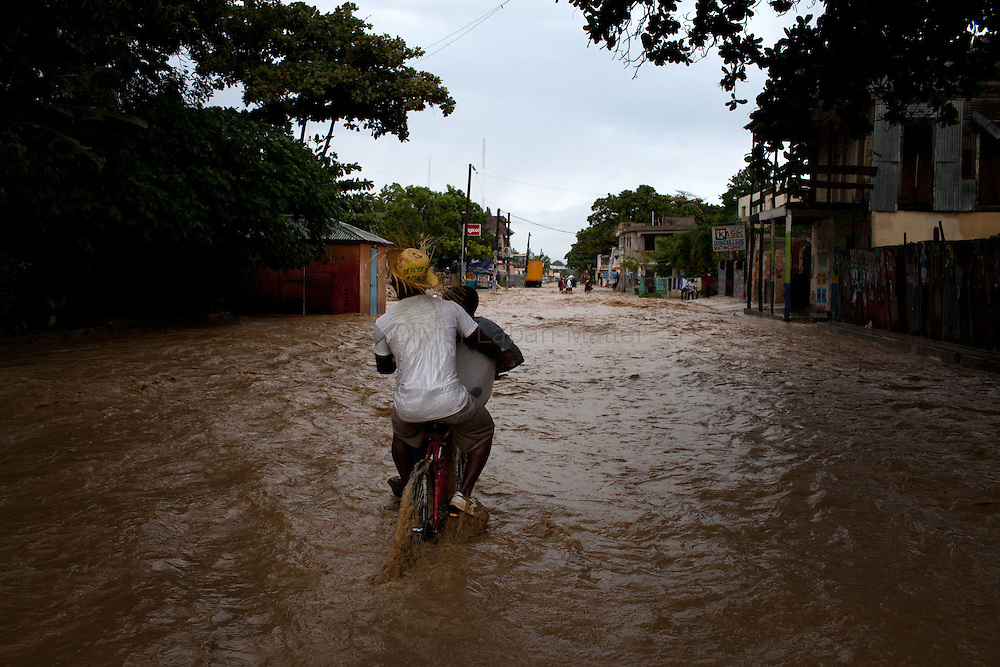 After hurricane Tomas went through Haiti, the city of Leogane has been totally flooded by the heavy rain and the overflow of the river Roullorne.///Two Haitian boys ride a bicycle in the the muddy water, in a street of Leogane during hurricane Tomas.