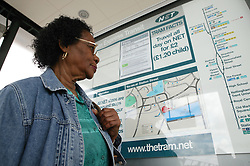 Woman looking at travel map at tram stop,