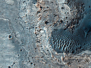 This image shows a number of unusual, quasi-circular structures from 300 to 600 meters in diameter that apparently formed within bright flows in Meridiani Planum.