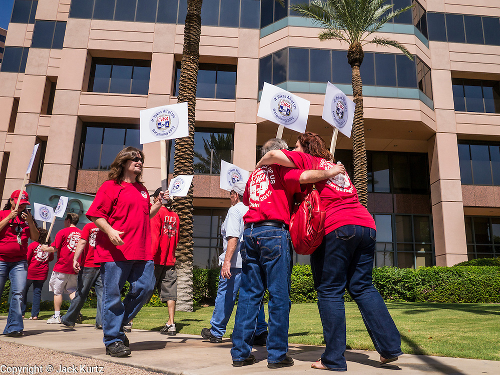 12 SEPTEMBER 2012 - PHOENIX, AZ: Members of the CWA hug during a picket of the CenturyLink offices. About 100 members of the Communication Workers of America (CWA) Local 7019 picketed the CenturyLink (formerly Qwest) offices in Phoenix Wednesday. The CWA and CenturyLink entered contract negotiations on August 15. The negotiations cover more than 15,000 workers across the western United States. Key issues include outsourcing and proposed cuts to retiree health benefits.    PHOTO BY JACK KURTZ