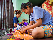 24 FEBRUARY 2015 - PHNOM PENH, CAMBODIA: Women who live in the White Building do sewing work on a landing. The White Building, the first modern apartment building in Phnom Penh, originally had 468 apartments, and was opened the early 1960s. The project was overseen by Vann Molyvann, the first Cambodian architect educated in France. The building was abandoned during the Khmer Rouge occupation. After the Khmer Rouge were expelled from Phnom Penh in 1979, artists and dancers moved into the White Building. Now about 2,500 people, mostly urban and working poor, live in the building. Ownership of the building is in dispute. No single entity owns the building, some units are owned by their occupants, others units are owned by companies who lease out apartments. Many of the original apartments have been subdivided since the building opened and serve as homes to two or three families. The building has not been renovated since the early 1970s and is in disrepair. Phnom Penh officials have tried to evict the tenants and demolish the building but residents refuse to move out.   PHOTO BY JACK KURTZ
