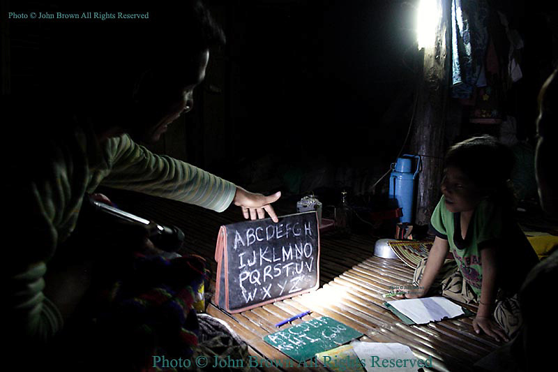 Sothea Touch, a former Buddhist monk who now works as an English teacher, gives an impromptu English lesson to his 8-year-old sister in Ban Russei, Cambodia. Since the family has no power, Sothea uses a flashlight to illuminate a briefcase he has written on with chalk.