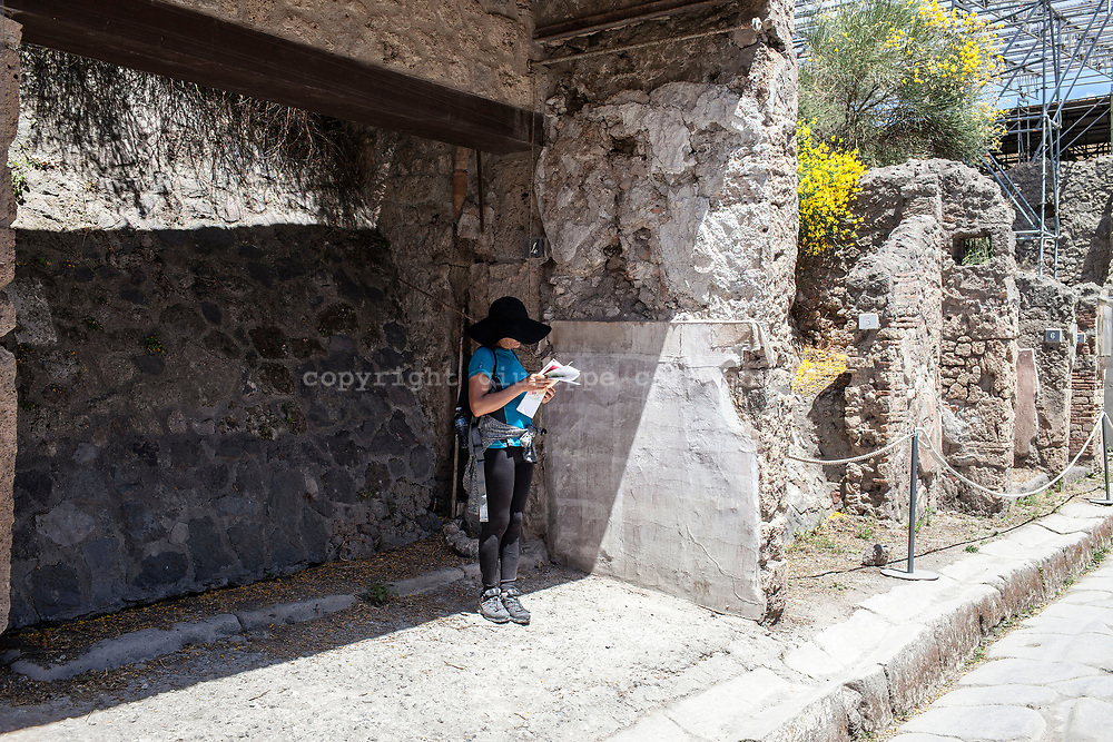"20 May 2017, Pompei, Naples Italy - A tourist inside the ancient city of Pompeii on the ""Via dell'abbondanza""."