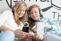 Sisters listening music through headphones at home