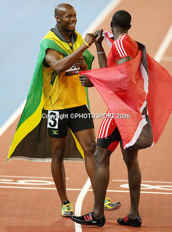 Jamaican athlete Asafa Powell (JAM) celebrates with Trinidad's Marc Burns (TRI) after winning the Men's 100M sprint on Day 5 of the XVIII Commonwealth Games at the MCG, Melbourne, Australia on Monday 20 March, 2006. Photo: Hannah Johnston/PHOTOSPORT<br />