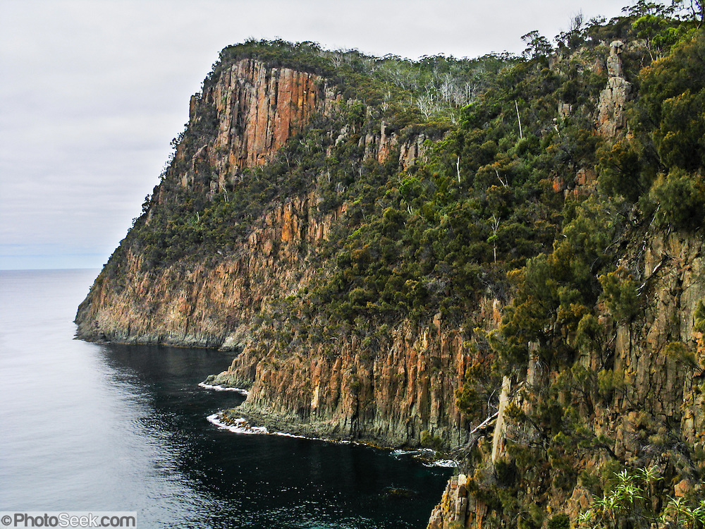 Admire coastal cliff scenery at Fluted Cape, South Bruny National Park, Bruny Island, Tasmania, Australia. Bruny Island lies just off the south-east coast of Tasmania. D'Entrecasteaux Channel separates the island from mainland Tasmania. Drive 40 km south of Hobart on Southern Outlet (A6) to Kingston and B68 to the Kettering vehicular ferry. The 15 minute ferry takes you to Roberts Point on north Bruny Island which has sealed & unsealed roads. The area offers good hiking, camping, birdwatching, and communing with nature.