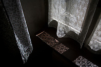 VERBANIA, ITALY - 18 APRIL 2017: Light filters through the window curtains in Emma Morano's small room in Verbania, Italy, on April 18th 2017.<br /> <br /> Emma Morano, born in 1899, was an Italian supercentenarian who, prior to her death at the age of 117 years and 137 days, was the world's oldest living person whose age had been verified, and the last living person to have been verified as being born in the 1800s. She died on April 15th 2017.
