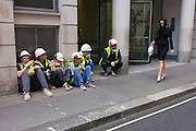 Workmen from a nearby construction site, admire a lone, young woman walking past in a City of London street.
