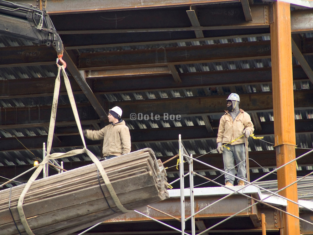Construction worker directs load of wood at job site