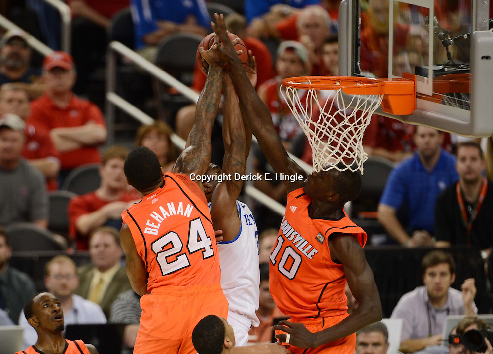 Mar 31, 2012; New Orleans, LA, USA; Kentucky Wildcats guard Marquis Teague (center) has his shot defended by Louisville Cardinals forward Chane Behanan (24) and center Gorgui Dieng (10) during the first half in the semifinals of the 2012 NCAA men's basketball Final Four at the Mercedes-Benz Superdome. Mandatory Credit: Derick E. Hingle-US PRESSWIRE