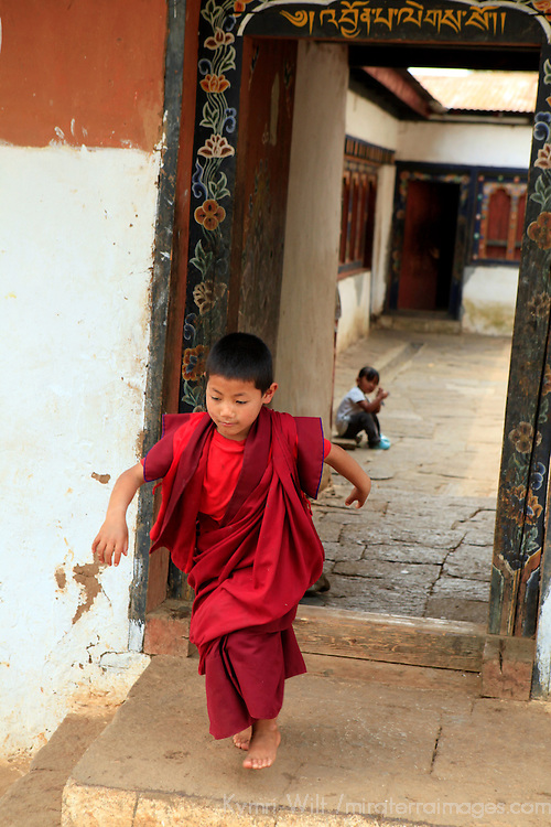 Asia, Bhutan, Sopsokha. A young Bhutanese monk skips out the doorway at Chimi Lhakhang.