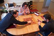 Justin King, Matthew Becker and Chris Meier play a match of Tsuro, a complicated tile-based game.  Players lay tiles down, creating complicated criss-crossing paths, while trying not to have their avatar piece touch the edges.  December 7, 2013.  Photo by Andrew Welsch/NYCity Photo Wire