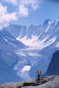A lone male mountain biker rests and enjoys the view of the Argentiere Glacier in the French Alps near Chamonix France.