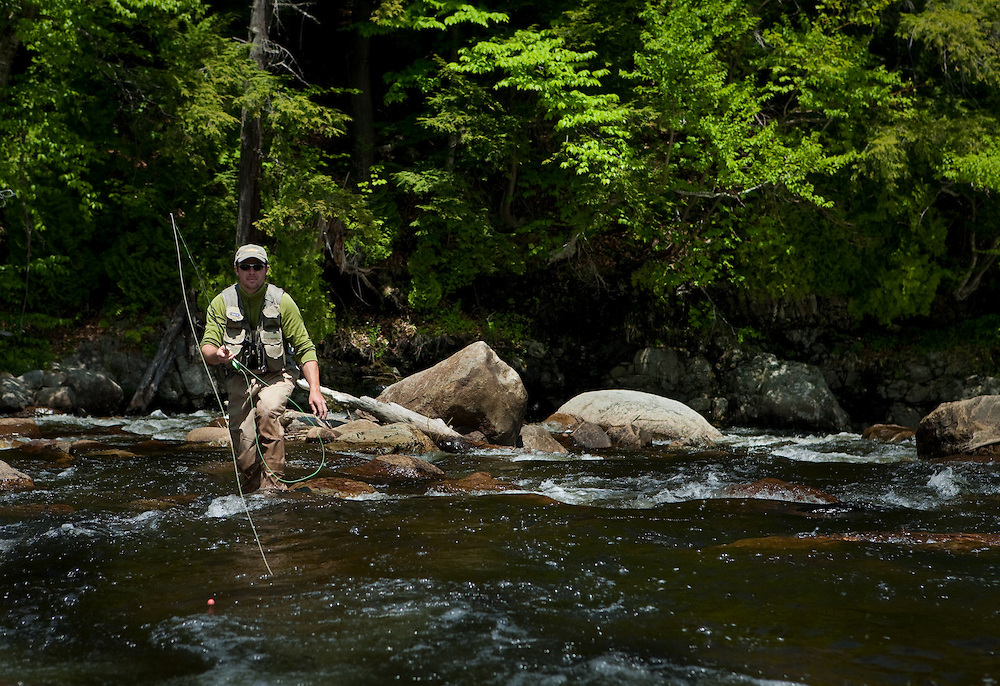 Male angler fly fishing for trout on the West Branch of the Ausable River in Wilmington, New York.