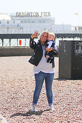 © Licensed to London News Pictures. 07/05/2015. Brighton, UK. A woman takes  photo with her child on Brighton Beach, Today Thursday May 7th 2015 Photo credit : Hugo Michiels/LNP