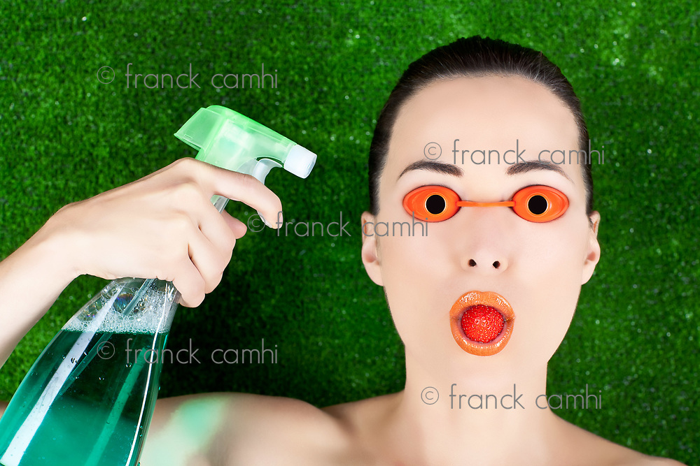 Closeup of a beautiful woman wearing tanning bed glasses with strawberry in mouth and spray bottle in hand against green