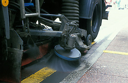 Cab driven street sweeper; close up of revolving brushes; North Shields; UK