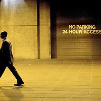 Male figure walking alone in street at night past access doorway