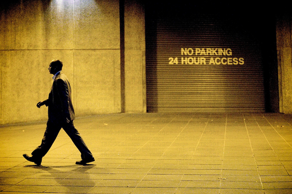 Male figure walking alone in street at night past access doorway