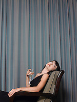 Woman sitting in chair holding champagne indoors