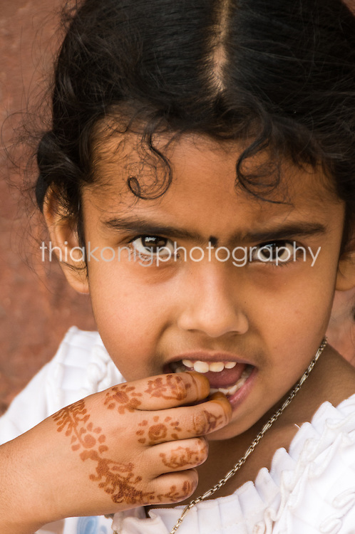 Portrait of young Indian girl with henna tatoo on her hands.