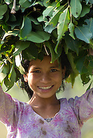 Beautiful young Tharu girl smiling and carrying leaf fodder on her head for her livestock, Terai region in Nepal