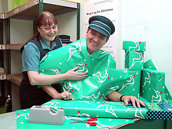 Lost Property Officer Sue Matthews (left) and Derby Statoin Manager Ken Elsey get wrapped up in Midland Mainlines Charity Christmas present wrapping service aimed at raising funds for local childrens hospitals.