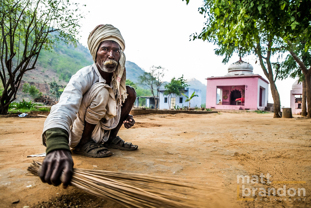 A village man sweeps the grounds around a Kali Temple.