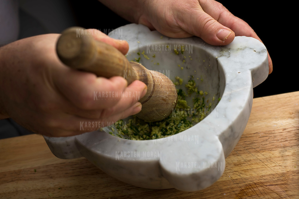 June 17, 2014 - New York, NY : David Tanis uses a mortar and pestle to make a chile and ginger paste to add to the batter as he prepaes dhokla, an Indian steamed bread.  CREDIT: Karsten Moran for The New York Times