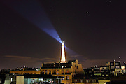 Each night a revolving light shines from the top of the Eiffel Tower in Paris.