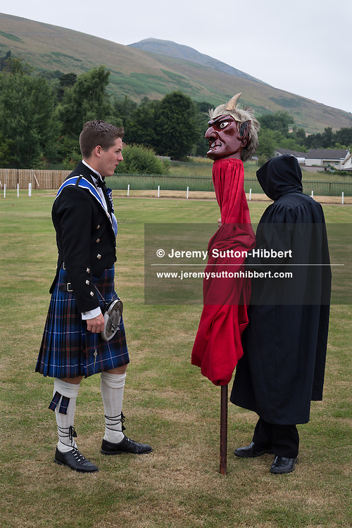 John Cockburn carries the De'il (the Devil) at St. Ronan's Games, in Innerleithen, in the Borders, Scotland, Saturday 20th July 2013. Standard Bearer Lyle Caine, St Ronan Dux Boy Kieran Frost, Dux Girl Emily McNeill.