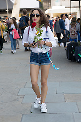 """© Licensed to London News Pictures. 11/06/2017. LONDON, UK.  A tourist walks through the new security bollards and barriers with a red rose this afternoon. 1,000 red roses with messages of """"love and solidarity"""" were given to passers by on London Bridge today.  Photo credit: Vickie Flores/LNP"""