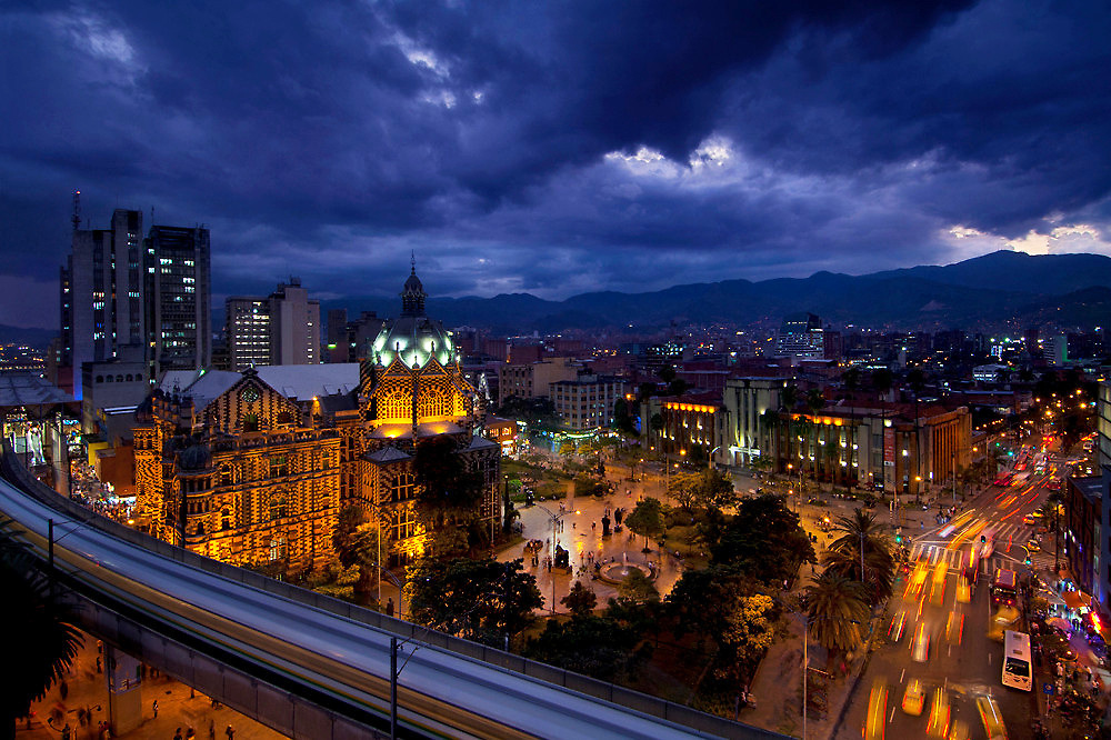 The elevated Medellin Metro is a blur as it rushes into the Parque Berrio Station in front of Plaza Botero.  The domed illuminated Palace of Culture and the art deco Museum of Antioquia frame the plaza. The plaza is named after Medellin's native son, and Colombia's most famous artist Fernando Botero, who donated 23 sculptures to sit in the plaza. A dramatic twlight sky outlines the Andes Mountains that surround the city in the Aburra Valley.