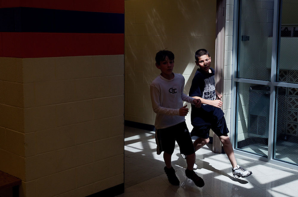 Sixth-graders Levi Hesman, left, and Caine ontiveros round a corner while running through the hallways with the run club Thursday at Barr Middle School. (Independent/Matt Dixon)