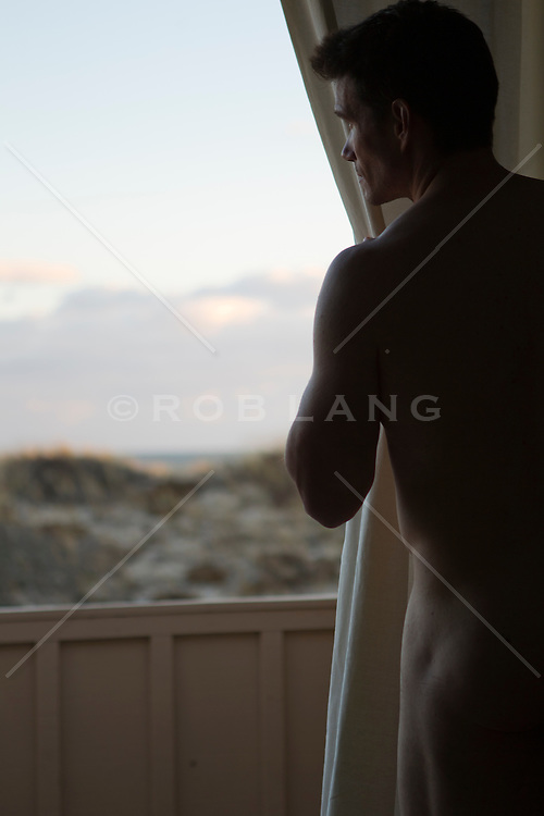 nude man looking out a balcony doorway overlooking the beach in The Hamptons
