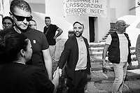 """NAPLES, ITALY - 30 JULY 2018: Roberto Saviano (center), an Italian journalist, writer and essayist greets a fan after stepping out of the collective """"Nuovo Teatro Sanità"""" (New Sanità Theatre) in the Sanità neighborhood in Naples, Italy, on July 30th 2018.<br /> <br /> In 2017 the 17-year-old innocent victim Genny Cesarano was shot and killed by stray bullet  in cross fire between 2 rival gangs vying for territorial control in the Sanità neighborhood.<br /> The  isolation of the neighborhood Sanità over the years provided an ideal location for the Camorra to expand their illicit activities and profit from soaring unemployment rates and economic instability,<br /> <br /> After the first death threats of 2006 by the Casalese clan , a cartel of the Camorra, which he denounced in his exposé and in the piazza of Casal di Principe during a demonstration in defense of legality, Roberto Saviano was put under a strict security protocol. Since 2006 Roberto Saviano has lived under police protection.<br /> <br /> Saviano's latest novel """"The Piranhas"""", which tells the story of the rise of  a paranza (or Children's gang) and it leader Nicolas, will be released in the United States on September 4th 2018."""