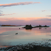 Maine, USA. sunset view from Vinelhaven island, 2 people rowing a boat.