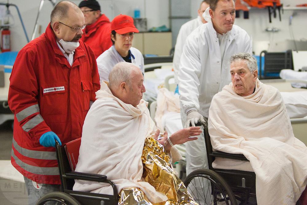 Twee slachtoffers worden met een rolstoel naar het ziekenhuis vervoerd.  In het Calamiteitenhospitaal in Utrecht wordt een rampenoefening gehouden. De nadruk ligt op de contaminatie, door een gekantelde vrachtwagen zijn veel slachtoffers in aanraking gekomen met een chemische stof. Voor het eerst wordt er geoefend met een zogenaamde decontaminatietent. Als de tent bevalt, schaft het ziekenhuis zo'n tent aan. Bij de 'ramp' zijn 100 slachtoffers gevallen.<br /> <br /> Two victim are transported to the hospital. In the Trauma and Emergency Hospital in Utrecht an calamity training was held. The emphasis is on the contamination by an overturned truck, many victims are contaminated by a chemical. For the first time a so-called decontamination tent was used. If the tent fulfills the expectations, a tent will be purchased. The 'calamity' caused 100 victims.