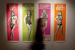 © Licensed to London News Pictures. 28/09/2012. LONDON, UK. A member of Christie's staff walks past a complete set of the four original cinema door poster used to advertise the film 'Thunderball' (1965) (est. £6,000-8,000) at the press view for the 50 Years of James Bond Auction in London today (28/09/12).  The auction, taking place on in two parts, an online sale on the 28th of September and an evening event on the 5th of October - Global James Bond Day -  is being held in aid of various charities and features props and costumes from 50 years of James Bond movies. Photo credit: Matt Cetti-Roberts/LNP