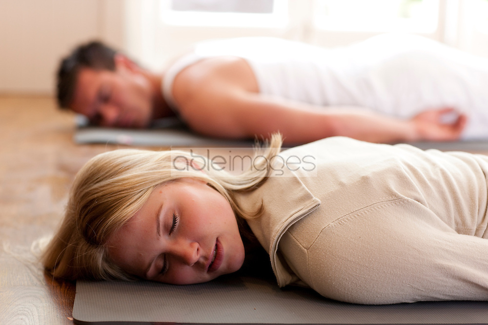 Man and woman relaxing during a yoga practice - close up