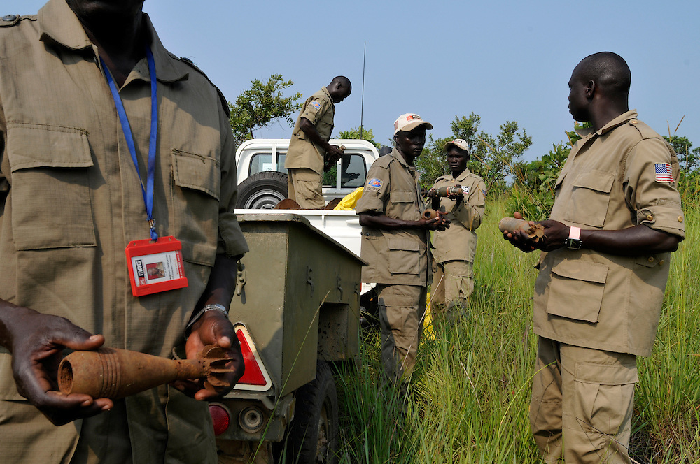 Members of the Mines Adivsory Group (MAG) MAT 2 Explosive Ordinance Disposal (EOD) team preparing a controlled demolition of a weapons stockpile found in a container in the middle of a village..Pageri, South Sudan. 30/06/2011..Photo © J.B. Russell
