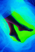 A woman's sexy legs surrounded by glowing veil in front of a green background.Black light