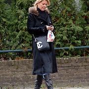 NLD/Bussum/20060104 - Bartina Koeman bellend en winkelend in Bussum met een Chanel tas, sms, mobiele telefoon, lange jas, laarzen, koud, tasje,