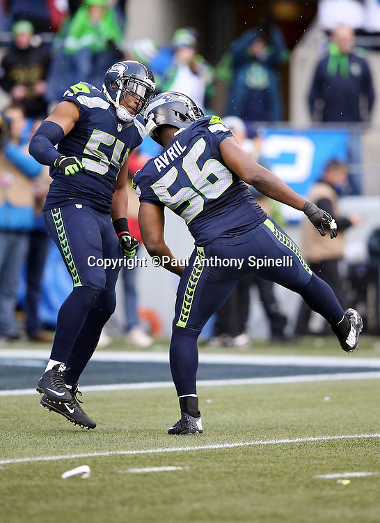 Seattle Seahawks middle linebacker Bobby Wagner (54) and Seattle Seahawks defensive end Cliff Avril (56) celebrate after Avril sacks Green Bay Packers quarterback Aaron Rodgers (12) for a 7 yard loss and forces a punt in the third quarter during the NFL week 20 NFC Championship football game against the Green Bay Packers on Sunday, Jan. 18, 2015 in Seattle. The Seahawks won the game 28-22 in overtime. ©Paul Anthony Spinelli