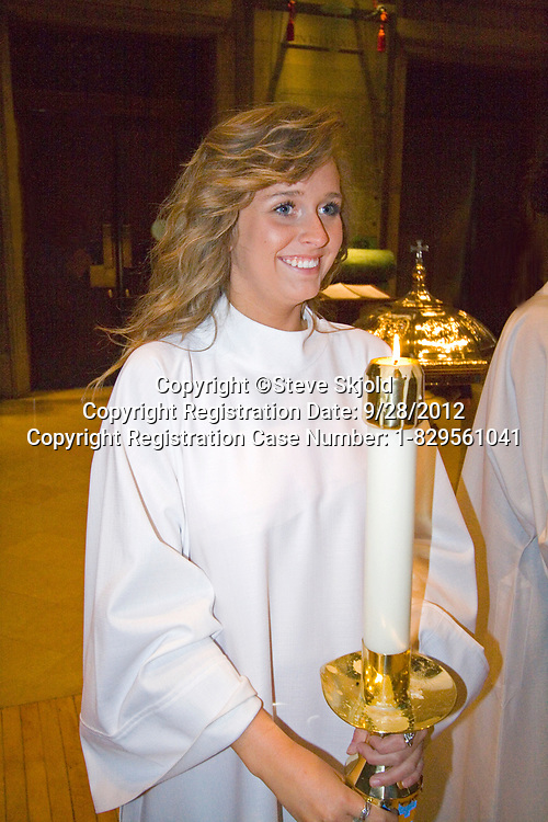 "Happy young woman acolyte candle bearer during Catholic Confirmation Mass. Basilica of ""St Mary"" Minneapolis Minnesota MN USA"