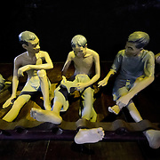 Detail of some of the sculptures illlustrating the conditions that inmates were kept in at Hoa Lo Prison, with one leg shackled to prevent movement. tHoa Lo Prison, also known sarcastically as the Hanoi Hilton during the Vietnam War, was originally a French colonial prison for political prisoners and then a North Vietnamese prison for prisoners of war. It is especially famous for being the jail used for American pilots shot down during the Vietnam War.