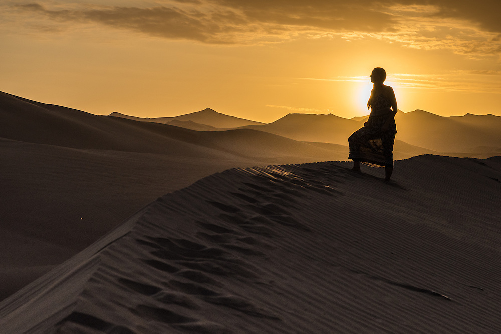 Woman stands on top of a sanddune at sunset near the town of Huacachina, Peru.